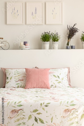 Floral bedding and pastel pink cushion on double bed in real photo of white bedroom interior with lavender, posters and decor