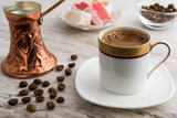 Vintage cup of turkish coffee and traditional bronze coffee pot served on marble with turkish delights - 218793473