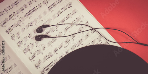 Headphones on music sheets. The concept of creating music. - 218828878