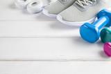 Fitness background - sneakers, dumbbell, earphones on white wooden board