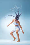 Attractive excited fitness girl dancer in sportwear. Wild dance isolated over blue background. Fashion and livestyle concept.