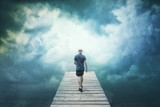 Man walking on wooden pier with artistic cloudscape background. - 218859683