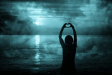 Silhouette of woman hands in heart shape with turquoise blue artistic sunset. - 218859692
