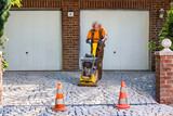 Builder or contractor laying new paving bricks. - 218867443