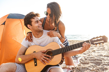 Young cute loving couple play guitar on the beach outdoors.