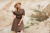 girl in a dress in a safari style and hat on sand background - 218920254