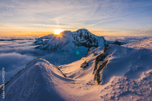 "Foto obraz na płótnie canvas trzyczęściowy - ""tryptyk"" - Stunning sunset or sunrise in winter alpine like snow landscape. Inversion, sun star peaking behind high rocky and icy summit. Purple, pink, blue and orange colors. Ladovy stit in winter High Tatras."