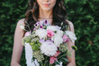 cropped view of beautiful woman posing in wedding dress and holding traditional bouquet