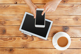 Girl hands with digital tablet and cup of coffee on a wooden table - 218924627