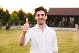 Image of happy young man 25-30 wearing white shirt smiling, and showing thumb up while walking outdoor on nature - 218931616