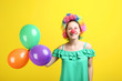 Young girl in clown wig and balloons on yellow background