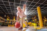 Professional player. Joyful nice man throwing the ball while playing bowling - 218947288