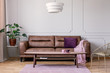 Real photo of brown leather sofa with violet cushion and pastel pink blanket standing in light grey sitting room interior with Monstera Deliciosa plant, molding on wall and coffee table