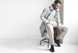 Fashion portrait of handsome  stylish man with dark beard and hair, weared in light trench coat, shirt, beige pants and black shoes. Man sits on the chair near white wall - 218972860