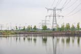 Torri per il trasporto della corrente elettrica situate sulla riva di un fiume - 218987259