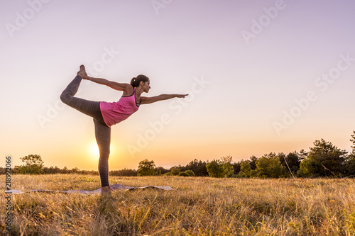 Poster Young beautiful woman practicing Yoga outdoor in nature during sunset