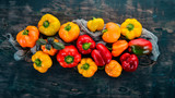Fresh Colored Paprika. Top view. On a black wooden background. Free space for text. - 219013864