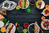 Oatmeal with yogurt, fruits and berries in plates. Breakfast. On a black wooden background. Top view. Free space for text. - 219014038