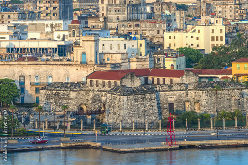 dilapidated stone buildings of an ancient city, the fence of a castle, car on the street