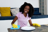 Happy african american woman cleaning room - 219027223