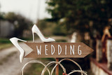 beautiful white shoes on wooden arrow with wedding text sign. rustic wedding concept. pointing for wedding ceremony location. creative ideas - 219030218