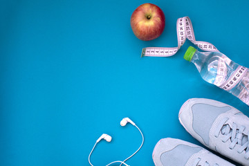 Fitness flat lay. Healthy lifestyle and sport concept. Blue sneakers, apple, bottle of water, tape measure and white earphones on a blue background.