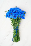 Blue Cornflower bouquet on white wooden background. Top view, copy space. Summer background