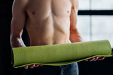 healthy and fit body. gym training. active wellness lifestyle. unrecognizable man preparing to exercise on a yoga mat. - 219076063