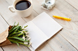 Cup of coffee, bouquet of flowers, notebook and the handle on a light wooden background