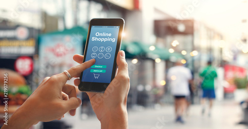 Man hands using smartphone for online shopping on city street background.  E-commerce icon network on screen. Digital marketing and Mobile payments. Online shopping concepts - 219079256