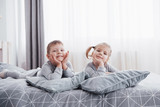 Happy kids playing in white bedroom. Little boy and girl, brother and sister play on the bed wearing pajamas. Nursery interior for children. Nightwear and bedding for baby and toddler. Family at home - 219080051