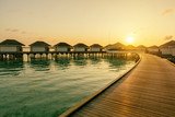 Tropical Water villas on Maldives island in sunrise time, holiday vacation background concept