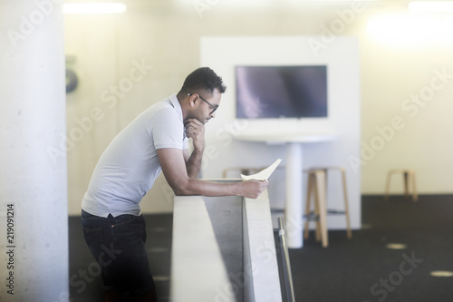 mata magnetyczna Junger Mann an einer Brüstung in einem Büro stehend