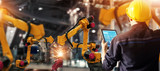 Engineer check and control welding robotics automatic arms machine in intelligent factory automotive industrial with monitoring system software. Digital manufacturing operation. Industry 4.0 - 219100685