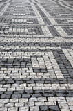 A footpath with a geometric pattern made by light and dark grey cobblestones. The stones are worn with age. - 219113079