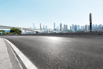 empty asphalt highway street with city skyline © zhu difeng