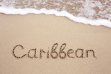 Word Caribbean written on the sand near the sea.