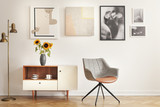 Grey armchair next to cupboard with sunflowers in white room interior with gallery. Real photo - 219127256