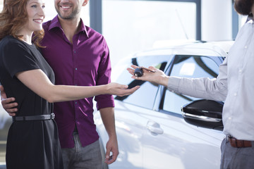 Car dealer giving keys to happy woman and smiling man in a dealing salon