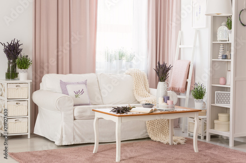 Real photo of bright provencal sitting room interior with white sofa, wooden coffee table on dirty pink carpet, rack with decor and fresh lavender © Photographee.eu