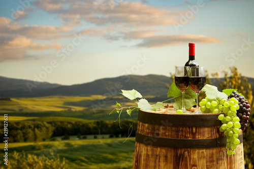 Red wine bottle and wine glass on wodden barrel. Beautiful Tuscany background - 219127631
