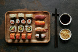 top view of assorted sushi set on wooden plate, chopsticks, ginger and soya sauce in bowls on dark tabletop - 219142218