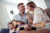 Couple playing acoustic guitar - 219154229