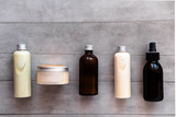 Bottles with spa cosmetic products from above on gray concrete table. Beauty blogger, salon treatments concept. Minimalism - 219167861