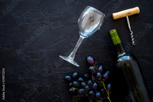 Composition with wine. Red wine bottle, bunch of grapes, corkscrew, wine glass on black background top view copy space - 219173254