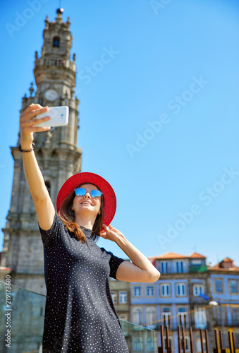 Leinwanddruck Bild Young beautiful girl in red hat take selfie with phone