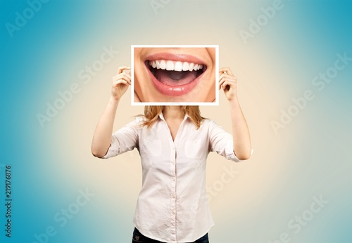 Leinwandbild Motiv Woman holding picture with big smile. concept photo over dark