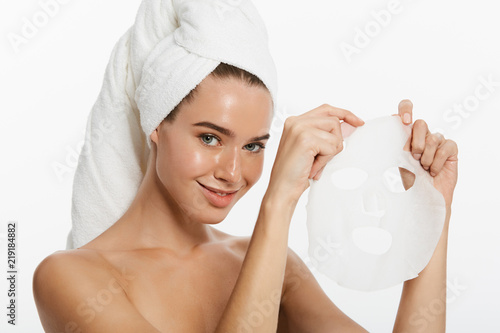 Leinwanddruck Bild Young girl with facial mask looking at camera over white background. Cosmetic procedure. Beauty spa and cosmetology.