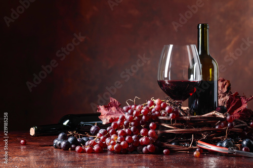 Red wine and fresh grapes with dried up vine leaves. - 219185258