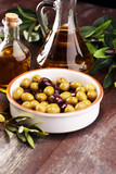 Olives. Bottle virgin olive oil and oil in a bowl with some olives - 219192823